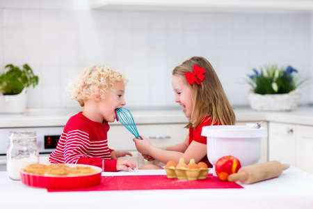 little dough: Cute kids, adorable little girl and blond curly boy making dough for a cake. Children mix flour, eggs and milk baking apple pie in sunny white kitchen with modern appliances. Family cooking at home.