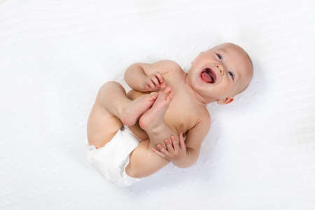 nappy: Funny little baby wearing a diaper playing on a white knitted blanket in a sunny nursery. Child after bath or shower on a fresh towel. Infant nappy change and skin care. Cute kid playing with his feet