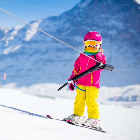 kids at the ski lift: Child on a button ski lift going uphill in the mountains on a sunny snowy day. Kids in winter sport school in alpine resort. Family fun in the snow. Little skier learning and exercising on a slope. Stock Photo