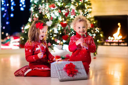 decorating: Happy little kids in matching red knitted sweaters decorate Christmas tree in beautiful living room with traditional fire place. Children opening presents on Xmas eve.