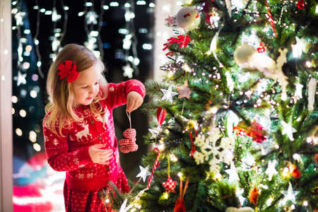 Little girl in red knitted Nordic reindeer sweater hanging ornaments on Christmas tree with light, bauble and candy canes. Child decorating Xmas tree in beautiful family living room with fireplace. Reklamní fotografie