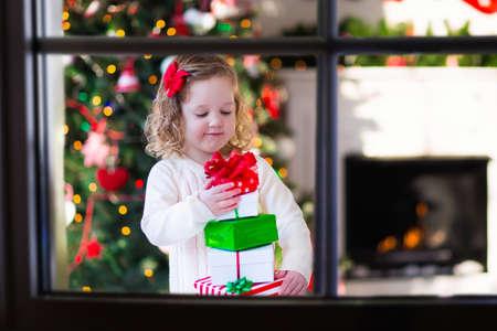 Familia en la mañana de Navidad en la chimenea. Niños abriendo regalos de Navidad. Niños bajo el árbol de Navidad con cajas de regalo. Sala de estar decorada con chimenea tradicional. Acogedor y cálido día de invierno en casa.
