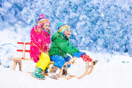 snow forest: Little girl and boy enjoy a sleigh ride. Child sledding. Toddler kid riding a sledge. Children play outdoors in snow. Kids sled in Alps mountains in winter. Outdoor fun for family Christmas vacation.