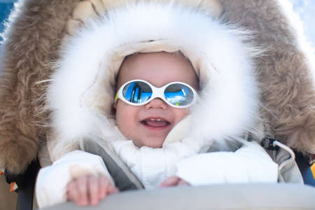 fur hood: Little baby in warm stroller wearing fur hood snow suit enjoying winter ski vacation in alpine resort. Eyewear and sun protection sunglasses for infants. Child in safe snow goggles in Alps mountains.