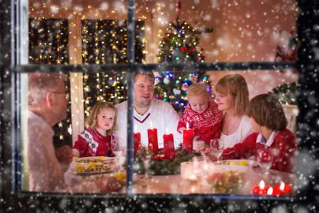 family together: Big family with three children celebrating Christmas at home. Festive dinner at fireplace and Xmas tree. Parent and kids eating at fire place in decorated room. Child lighting advent wreath candle.