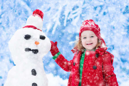 having fun in winter time: Funny little toddler girl in a red knitted Nordic hat and warm coat playing with a snow man. Kids play outdoors in winter. Children having fun at Christmas time. Child building snowman at Xmas.