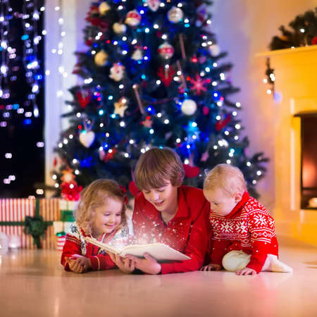 christmas winter: Children read a book and open gifts at fireplace on Christmas eve. Family with child celebrating Xmas. Decorated living room with tree, fire place, candles. Winter evening at home for parents and kids