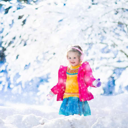 having fun in winter time: Funny little toddler girl in a colorful knitted hat and warm coat playing with snow. Kids play outdoors in winter. Children having fun at Christmas time. Child enjoying sunny day during Xmas vacation. Stock Photo