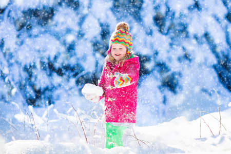 snow  snowy: Child running in snowy forest. Toddler kid playing outdoors. Kids play in snow. Christmas vacation in sunny winter park for family with young children. Little girl in colorful jacket and knitted hat.
