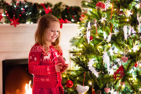 sueteres: Little girl in red knitted Nordic reindeer sweater hanging ornaments on Christmas tree with light, bauble and candy canes. Child decorating Xmas tree in beautiful family living room with fireplace. Foto de archivo