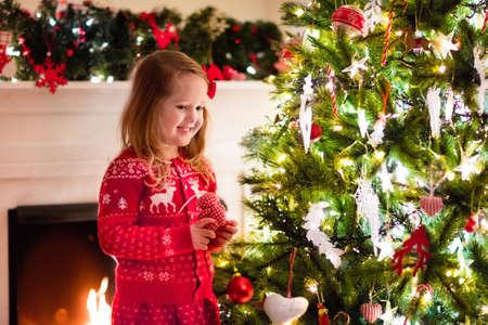 sueter: Niña en reno rojo nórdico ornamentos colgantes del suéter de punto en el árbol de Navidad con la luz, la chuchería y bastones de caramelo. Niño que adorna el árbol de Navidad en la hermosa sala de estar con chimenea.