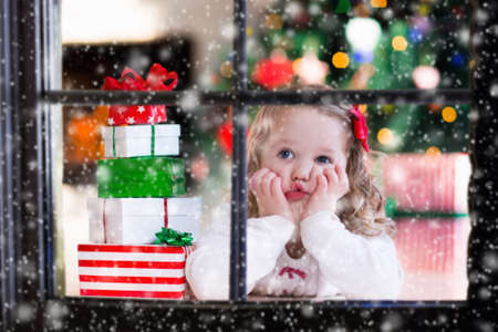 Little girl waiting for Santa at home window on Christmas eve. Kids opening Xmas presents. Child under Christmas tree with gift boxes. View from outside. Winter snowy day at home. Stock Photo