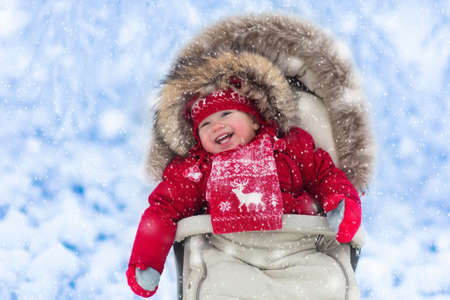 Happy laughing baby in warm red down jacket and knitted Nordic hat and scarf on a walk in a snowy winter park sitting in warm stroller with sheepskin hood catching snow. Child in buggy with foot muff Stock Photo