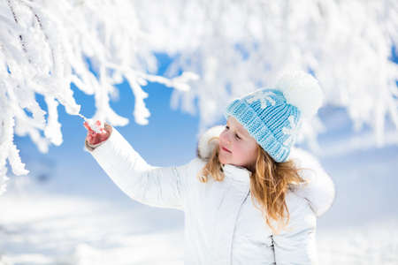 snow forest: Child in white jacket with fur hood and blue knitted snowflake hat playing in snowy forest on sunny winter day. Toddler kid girl having fun outdoors during Christmas vacation. Kids play in snow. Stock Photo