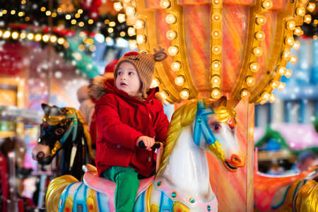 Happy little girl in warm red jacket and knitted reindeer hat riding carousel horse during family trip to traditional German Christmas market. Kids at Xmas outdoor fair on snowy winter day. Stock Photo