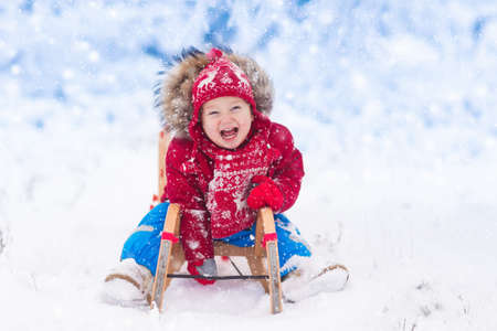 Little girl enjoying a sleigh ride. Child sledding. Toddler kid riding a sledge. Children play outdoors in snow. Kids sled in the Alps mountains in winter. Outdoor fun for family Christmas vacation. Фото со стока