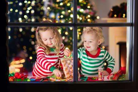 男の子と女の子の装飾が施されたリビング ルームの暖炉のそばでクリスマスのジンジャーブレッド家を作るします。生姜で遊ぶ子供たちは、クリス 写真素材