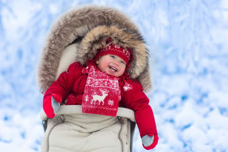 sheepskin: Happy laughing baby in warm red down jacket and knitted Nordic hat and scarf on a walk in a snowy winter park sitting in warm stroller with sheepskin hood catching snow. Child in buggy with foot muff Stock Photo