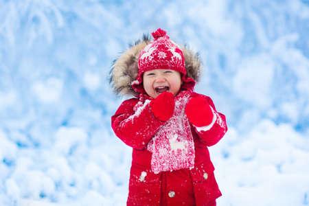 Dziecko bawi się ze śniegiem w zimie. Mały chłopiec maluch w czerwonej kurtce i Xmas reniferów czapka łowienie śniegu w zimie park na Boże Narodzenie. Dzieci grają w snowy lasu. Dzieci złapać płatki śniegu