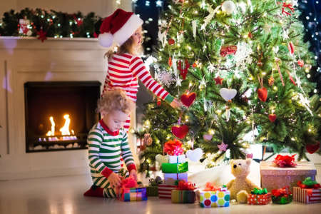 striped pajamas: Happy little kids in matching red and green striped pajamas decorate Christmas tree in beautiful living room with traditional fire place. Children opening presents on Xmas eve. Focus on girl