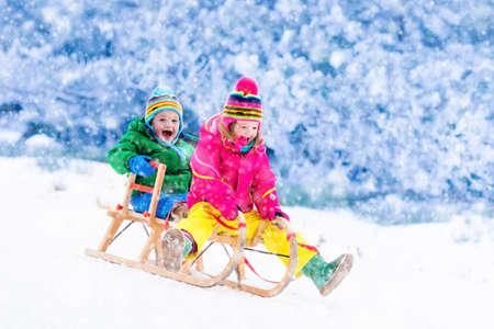 少女と少年は、そりの乗車をお楽しみください。そりの子。幼児の子供がそりに乗って。雪の中で子供を促します。子供たちは冬のアルプス山脈の