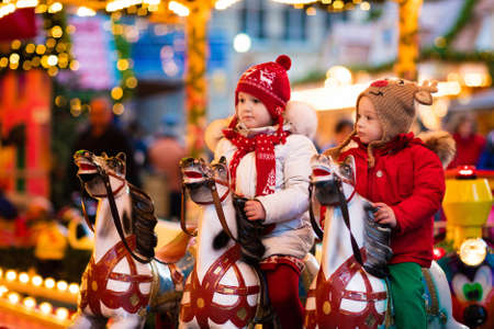 Happy little girl and boy in warm jacket and red knitted Nordic hat and scarf riding carousel horse during family trip to traditional German Christmas market. Kids at Xmas outdoor fair on snowy winter day. Stockfoto