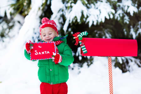 post mail: Happy child in knitted reindeer hat and scarf holding letter to Santa with Christmas presents wish list at red mail box in snow under Xmas tree in winter forest. Kids sending post to North Pole.