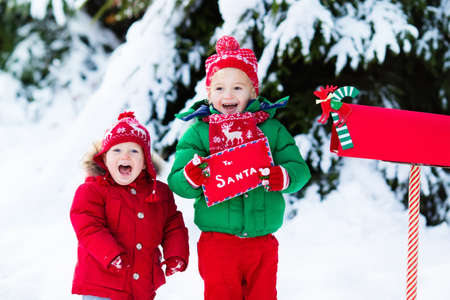 Happy children in knitted reindeer hat and scarf holding letter to Santa with Christmas presents wish list at red mail box in snow under Xmas tree in winter forest. Kids sending post to North Pole. Stock Photo