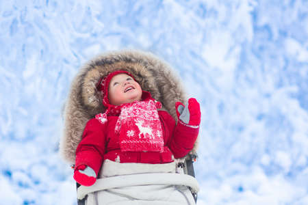 muff: Happy laughing baby in warm red down jacket and knitted Nordic hat and scarf on a walk in a snowy winter park sitting in warm stroller with sheepskin hood catching snow. Child in buggy with foot muff Stock Photo