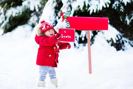 neige noel: Heureux enfant en tricot chapeau de renne et une écharpe lettre de maintien de Père Noël avec des cadeaux de Noël liste de souhaits à la boîte aux lettres rouge dans la neige sous l'arbre de Noël dans la forêt d'hiver. Les enfants envoient poste à Pôle Nord.