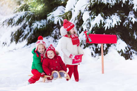 post mail: Happy children in knitted reindeer hat and scarf holding letter to Santa with Christmas presents wish list at red mail box in snow under Xmas tree in winter forest. Kids sending post to North Pole. Stock Photo