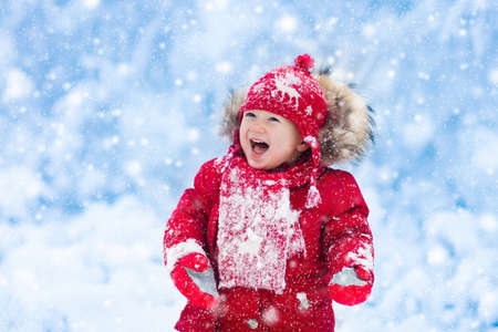 snow  snowy: Baby playing with snow in winter. Little toddler boy in red jacket and Xmas reindeer knitted hat catching snowflakes in winter park on Christmas. Kids play in snowy forest. Children catch snow flakes
