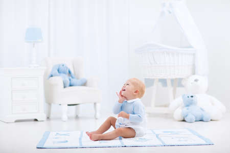 Adorable baby boy playing in white sunny bedroom. Happy child relaxing in toy chair on play mat. Nursery and play room for young children. Infant furniture, clothing, textile and bedding for kids.