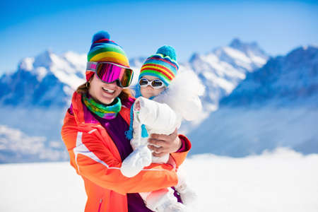 ski walking: Young mother and little baby enjoying winter ski vacation in alpine resort. Eyewear and sun protection sunglasses for infants. Family with safe goggles walking in the snow in the Alps mountains. Stock Photo