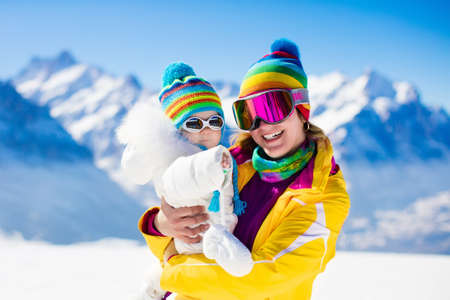 Young mother and little baby enjoying winter ski vacation in alpine resort. Eyewear and sun protection sunglasses for infants. Family with safe goggles walking in the snow in the Alps mountains. Stock Photo