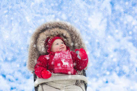 Happy laughing baby in warm red down jacket and knitted Nordic hat and scarf on a walk in a snowy winter park sitting in warm stroller with sheepskin hood catching snow. Stock Photo