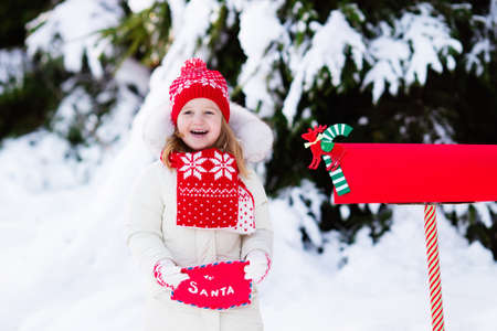 Happy Child In Knitted Reindeer Hat And Scarf Holding Letter Stock
