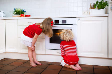 baking oven: Little boy and girl, brother and sister baking delicious apple pie in white kitchen. Kids looking at fruit cake in the oven. Children bake at home. Toddler child and preschooler waiting for pastry. Stock Photo