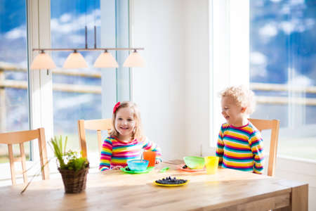comiendo cereal: Children enjoying breakfast in sunny kitchen with big windows. Kids eating fruit cereal and berry and drinking milk or juice before kindergarten or preschool. Healthy nutrition for toddler and baby. Foto de archivo