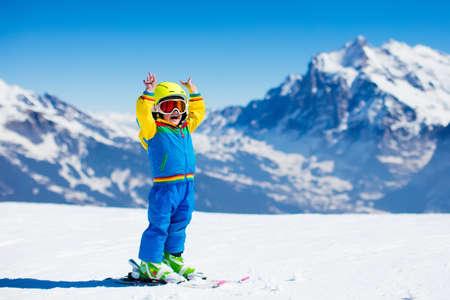 Kind skiën in de bergen. Actieve peuter jongen met veiligheidshelm, veiligheidsbril en palen. Ski race voor jonge kinderen. Wintersport voor familie. Kids ski les in alpine school. Weinig skiër racen in de sneeuw