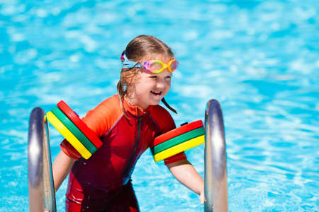 happy laughing little girl playing in outdoor swimming pool on a hot summer day in sun protection rash guard.