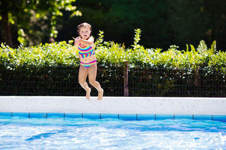 Happy little girl jumping into outdoor swimming pool in a tropical resort during family summer vacation. Stock Photo