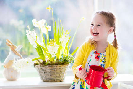 Cute girl watering first spring flowers. Easter home interior and decoration.
