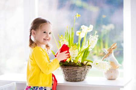 Cute girl watering first spring flowers.