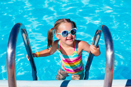 armbands: Happy laughing little girl playing in outdoor swimming pool on a hot summer day.