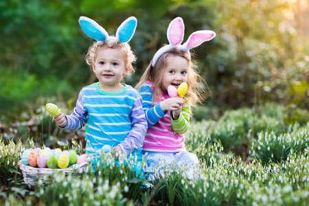 Kids on Easter egg hunt in blooming spring garden. Stock Photo