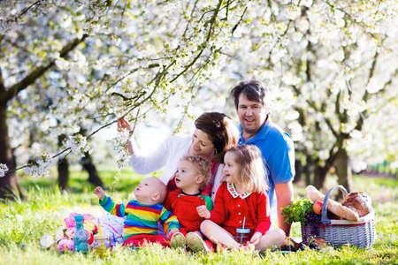 almuerzo: gran familia con tres niños pequeños que comen el almuerzo al aire libre.