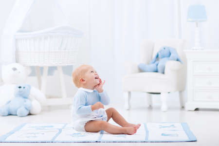 Adorable baby boy playing in white sunny bedroom. Фото со стока