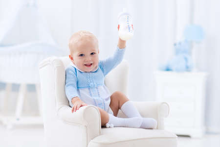 Adorable baby boy playing on a blue floor mat and drinking milk from a bottle in a white sunny nursery with rocking chair and bassinet.