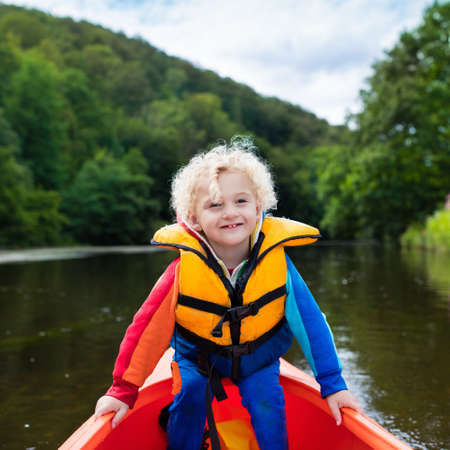 Happy kid enjoying kayak ride on beautiful river. Little curly toddler boy kayaking on hot summer day. Water sport and camping fun. Canoe for children. Funny child with vessel in a boat. Reklamní fotografie